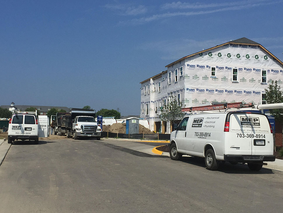 MEP Partners LLC., vans parked in front of a new residential building in process